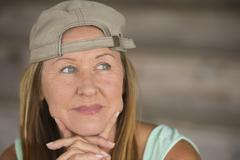 Active fit smiling mature woman sporty cap - stock photo