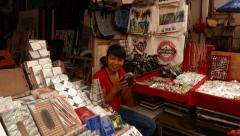 Indonesian girl selling souvenirs play tiny stringed instrument Stock Footage