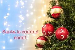 Closeup of xmas-tree decorations with Santa coming sign - stock photo