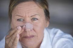 Unhappy woman with band aid on injured nose - stock photo