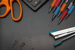 Closeup office stationery on black background, back to shcool concept Stock Photos