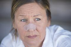 Sad woman with band aid on injured nose - stock photo
