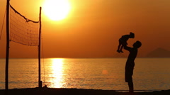 Silhouette of father playing with kid on beach at sunrise Stock Footage