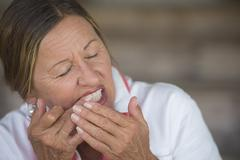 Mature Woman toothache in pain portrait - stock photo