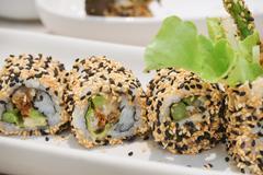 Maki Sushi - Roll with avocado,  Sesame outside. Stock Photos