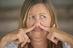 Woman annoyed by smelly air blocking nose Stock Photos