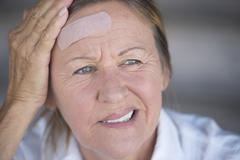 Woman with painful headache and band aid Stock Photos