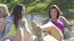 Teen Girls Ride Around Lake In Pedal Boat, One Girl Pedals, The Others Relax - stock footage