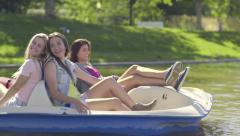 One Girl Does All The Pedaling, Her Friend Relaxes, Gives Her The Peace Sign - stock footage
