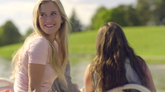 Pretty Teen Smiling In The Back Of A Pedal Boat, Her Friend Turns And Smiles Stock Footage