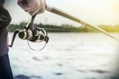 hand holding a fishing rod with reel - stock photo