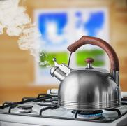 Kettle boiling on the gas stove in the kitchen Stock Photos