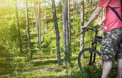 Extreme cyclist on the background of pine forest - stock photo
