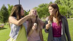 Teens Eat Ice Cream, Girls Tease Their Friend, Try To Get Ice Cream On Her Stock Footage