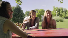 Girls Eat Snacks At A Picnic Table, Offer Bites To Their Friend, It's Funny Stock Footage