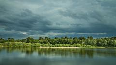 The puffy clouds above forest and river (lake) Stock Photos