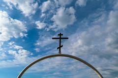 White semi-circular arch of iron pipe with dark Orthodox cross on it Stock Photos