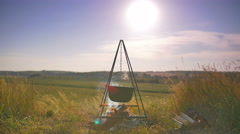 4 in 1 video! Cauldron with food on the fire by picturesque landscape backround - stock footage