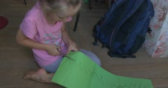 Little Girl in Oink T-Shirt is Sitting on The Floor With Color Paper in Front Stock Footage