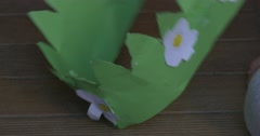 Little Girl in Oink T-Shirt is Sitting on The Floor With Green Paper Crown in Stock Footage
