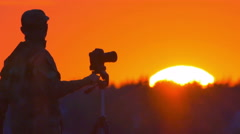 The photographer work with camera on the tripod by huge sun background - stock footage