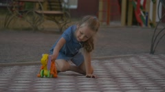 Little girl in blue dress plays a toy dog in the yard Stock Footage
