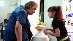 The old woman and the girl in contact with a silent robot. New technologies. Stock Footage