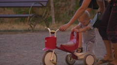 A little boy is taught by mom to drive a tricycle Stock Footage