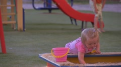 Baby, Little Girl in Pink is Playing in a Sandbox, Looking at the Children on a Stock Footage