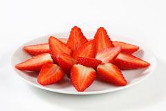 Halved strawberries arranged on plate - stock photo