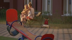 Women, Moms, Are Sitting on The Bench And Talking, Red Teeter-Totter on Stock Footage