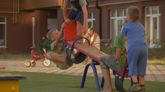 Boys, Children Are Swinging on Teeter-Totter, Tricycle, Moms with Their Stock Footage