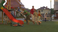 Little kids run one after another on the playground in yard Stock Footage