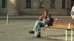 Authentic emotion handicapped homeless man sitting on a bench and eating - stock footage