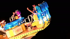 PASSENGERS SCREAMING IN FAST TURNING CAROUSEL AT NIGHT Stock Footage