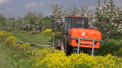 Agriculture tractor spray fertilize blossoming apple orchard  garden in spring Stock Footage