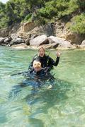 Male and female scuba divers - stock photo