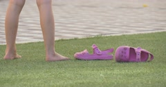 A little girl stands on grass Stock Footage