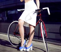 young beautiful blonde in city with bicycle drinks water - stock photo