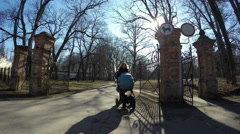 Nanny with blue stroller walk retro park gate in spring. 4K - stock footage
