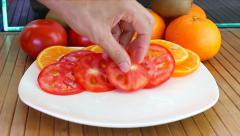 Slicing oranges, kiwi, tomato, fresh organic on plate Stock Footage