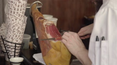 A man slicing some Jamon iberico at the market. Stock Footage