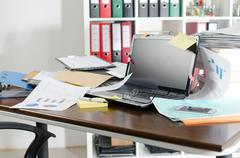Untidy and cluttered desk - stock photo