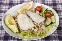Hake on Fried Jasmine Rice with Lemon, Avocado and Salad Stock Photos