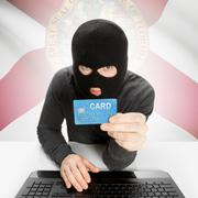 Hacker holding credit card with US state flag on background - Florida - stock photo