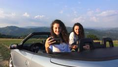 Young girls taking picture with cell phone from convertible cabriolet car Stock Footage