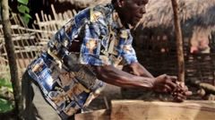 Daily life, Africa, Village man lumberjack sawing trunk profile Guinea Bisseau - stock footage