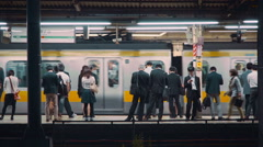 Commuters waiting to board trains at the subway station in Tokyo Stock Footage