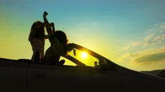 Young teen party. Silhouette sunset dance in cabriolet convertable car - stock footage