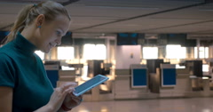 Woman with Tablet by Airport Check-In Counters Stock Footage